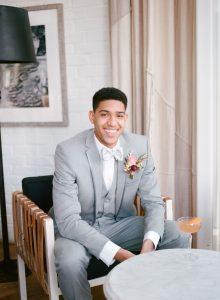 grey tuxedo groom peach pink magenta boutonniere