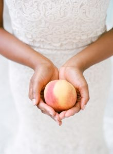 bride in lace wedding dress holding peach