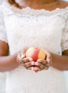 bride in lace wedding dress holding peach with wedding ring