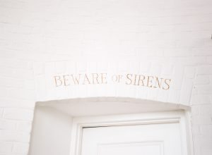 golden deware of sirens sign on white brick wall
