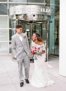 bride groom grey tuxedo lace off the shoulder wedding dress pink bridal bouquet
