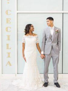 grey tuxedo black dress shoes white lace off the shoulder wedding dress pink purple peach boutonniere