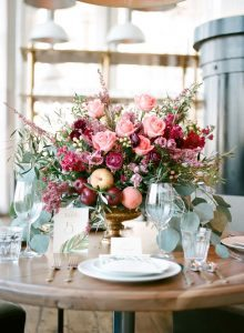 simple pink peach magenta floral centerpiece wedding reception table restaurant venue golden calligraphy escort cards