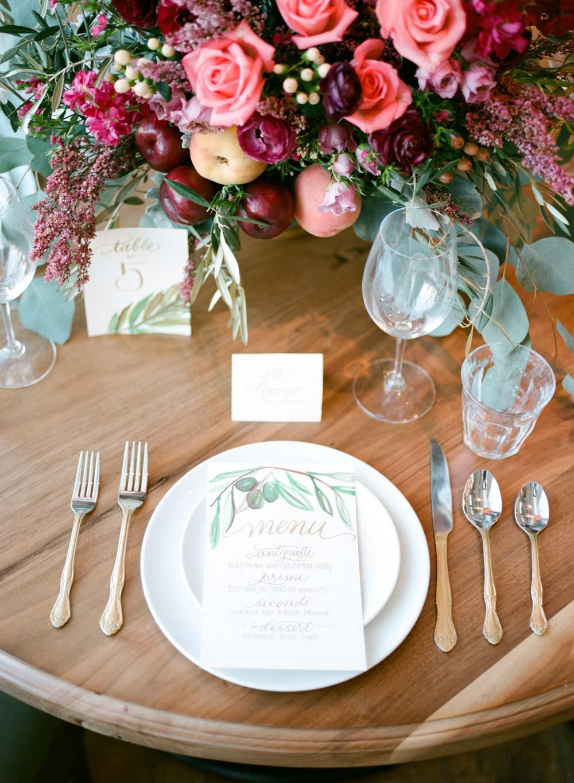 simple pink peach magenta floral centerpiece wedding reception table restaurant venue golden calligraphy escort cards table setting