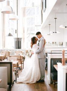 simple off the shoulder lace wedding dress half up half down braided bridal hair style grey tuxedo restaurant wedding venue
