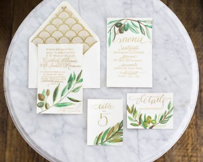 gold calligraphy wedding invitations with green leaf details