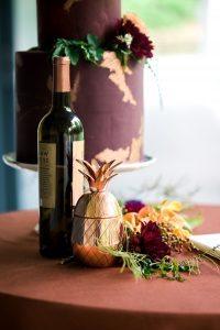 gold pineapple wedding decor wine table maroon yellow orange magenta flowers