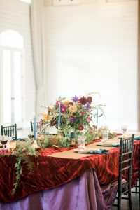 red purple velvet tablecloth multicolored floral centerpiece gold accent pieces wedding reception place setting