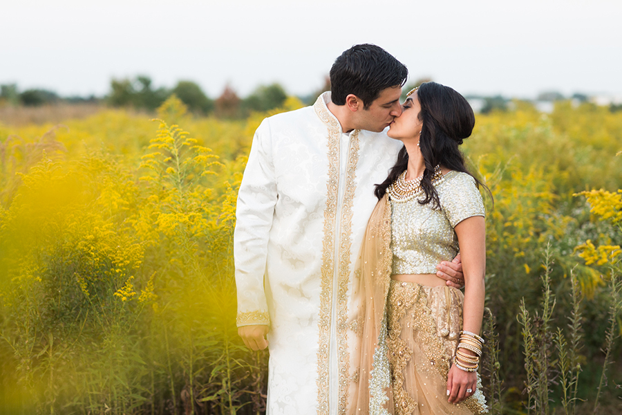 Bride and groom in gold and white kissing in field