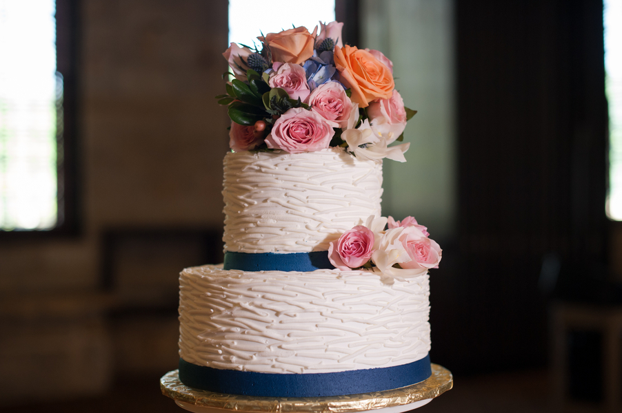 Navy ribbon wedding cake with flowers