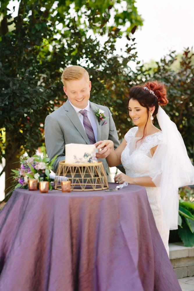 garden party bride and groom cutting cake