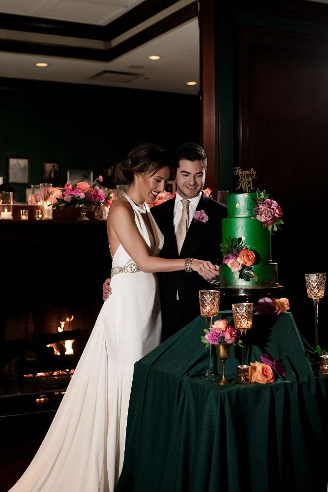 styled shoot the clubhouse cutting wedding cake