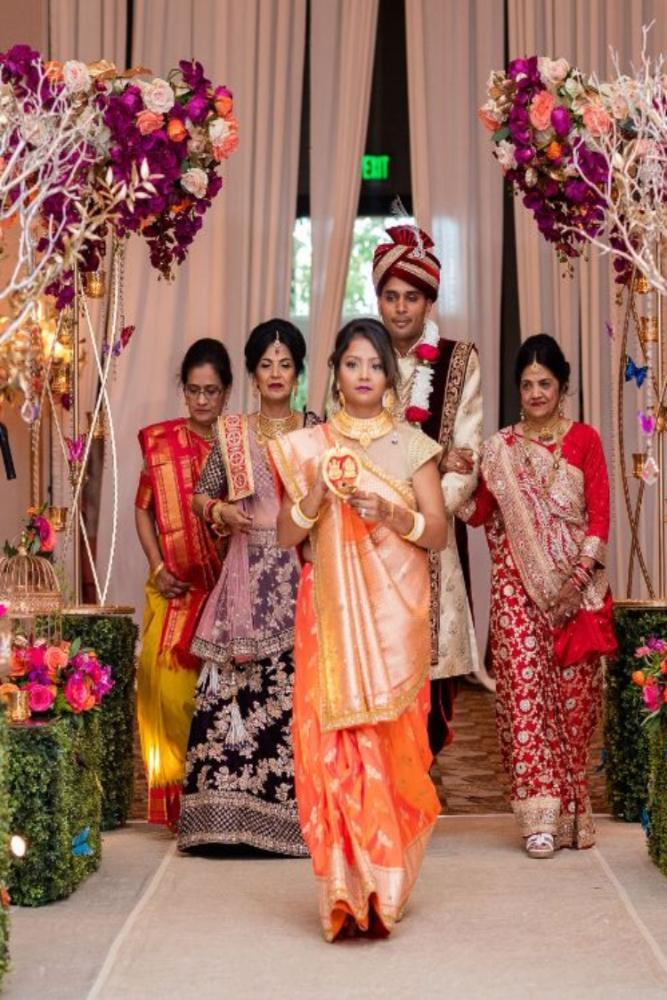 kajal akash pearl banquets & conference center wedding ceremony groom entering with women in colorful saris