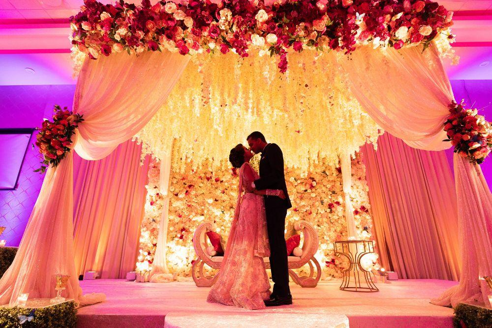 kajal akash pearl banquets & conference center bride and groom floral mandap kiss