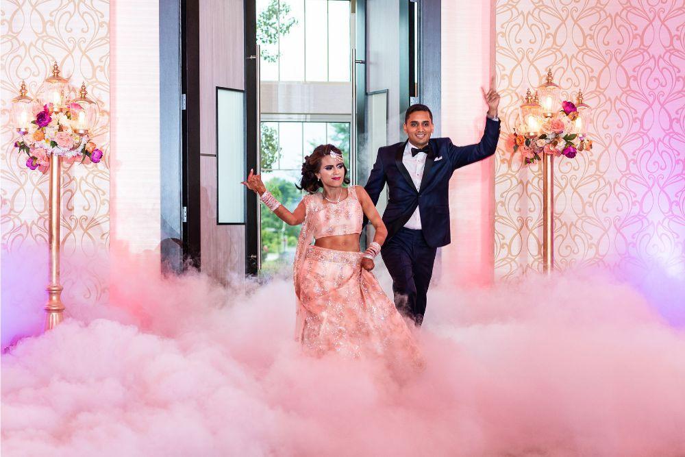 kajal akash pearl banquets & conference center bride and groom entering wedding reception with fog