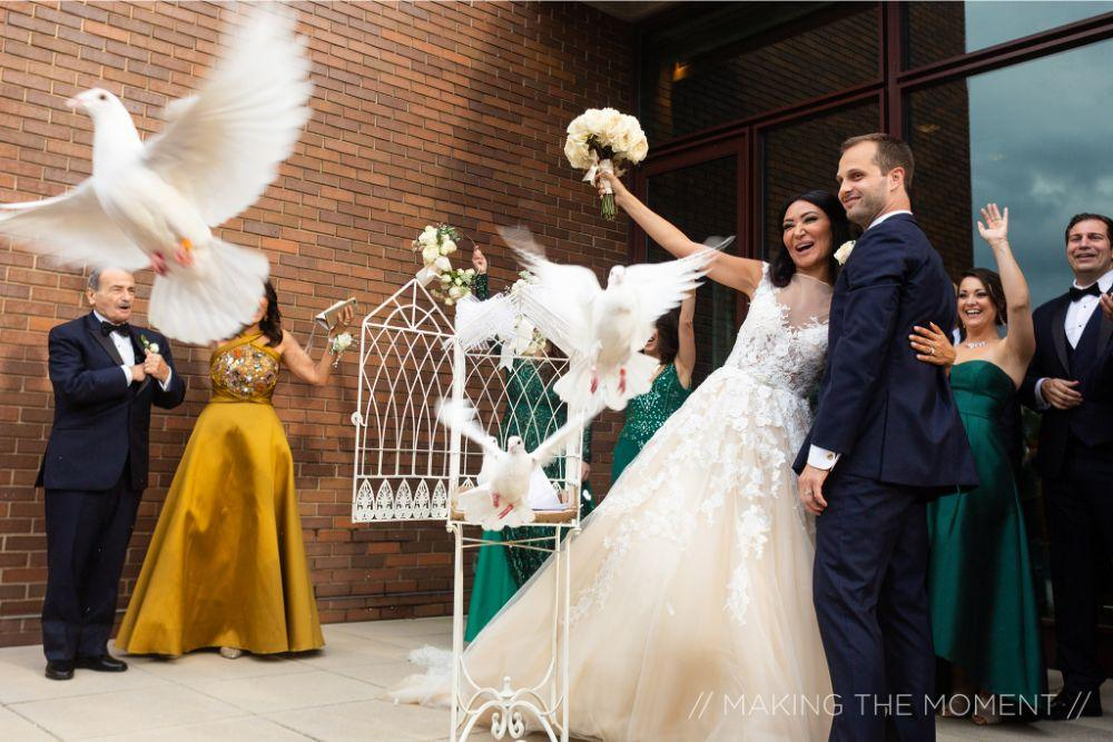 grace nicholas the hyatt lodge oak brook, IL doves bride and groom exit from church