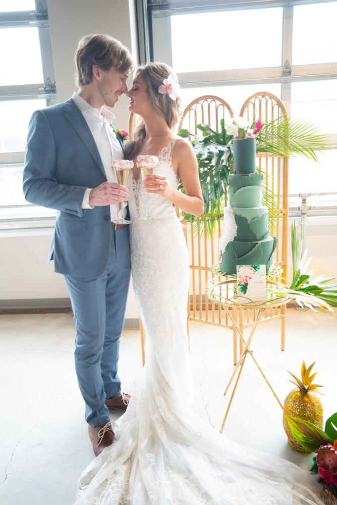 vibrant tropical paradise wedding inspiration at gallery 1500 bride and groom toasting with wedding cake