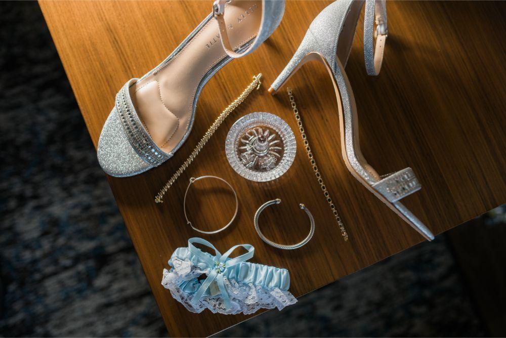 megan mike hotel indigo naperville rivewalk chicago wedding details flat lay with bridal shoes jewelry and garter