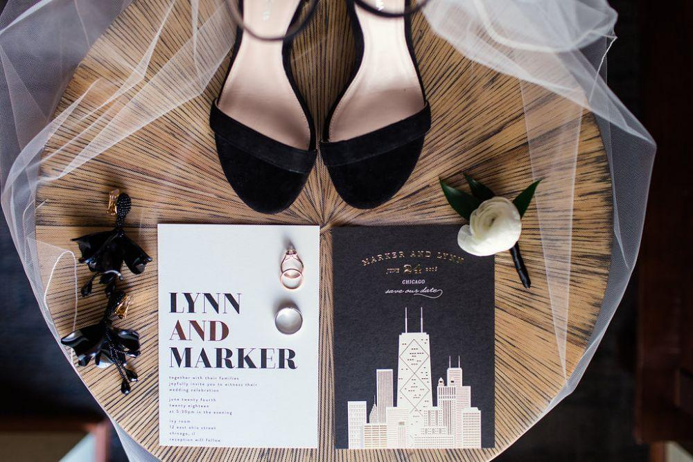 The Ivy Room at Tree Studios wedding invitation details flat lay with shoes veil and rings