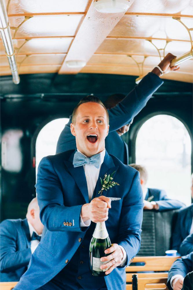 kathy michael skyline loft bridgeport art center chicago wedding groom popping champagne on party trolley