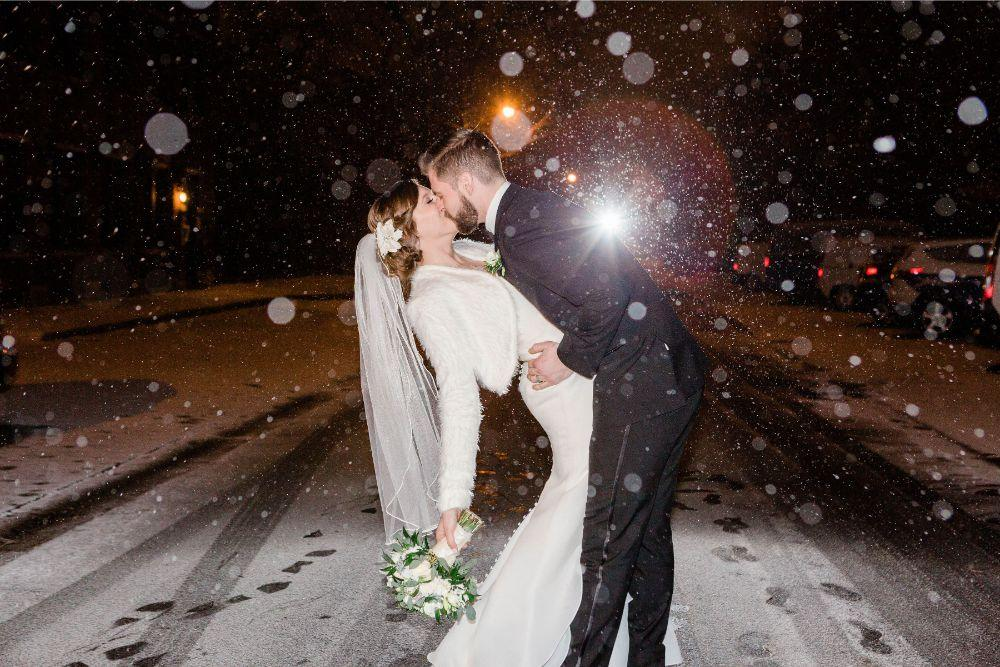 emily nick artifact events chicago, il wedding bride and groom kiss in the snow